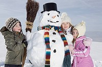 Germany, Bavaria, Munich, Children 4_5 8_9 standing next to snowman, portrait