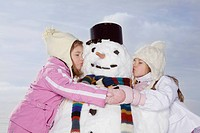 Germany, Bavaria, Munich, Two girls 4_5 8_9 kissing snowman, eyes closed, portrait