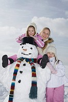 Germany, Bavaria, Munich, Mother and daughters 4_5 8_9 standing next to snowman, smiling, portrait