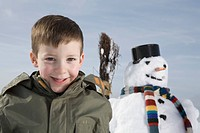 Germany, Bavaria, Munich, Boy 8_9 smiling, snowman in background