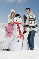 Germany, Bavaria, Munich, Family making a snowman, portrait