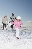 Germany, Bavaria, Munich, Familiy running across snowy landscape