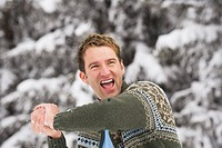 Italy, South Tyrol, Young man with snowball, laughing, portrait