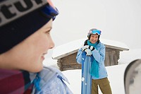 Italy, South Tyrol, Young couple in winter clothes, cabin in background