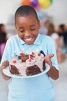 Young boy looking at his birthday cake