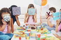 Kids holding gifts over face at party