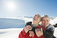 Italy, South Tyrol, Seiseralm, Senior couple embracing in winter scenery, portrait, close_up