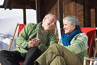 Italy, South Tyrol, Seiseralm, Senior couple sitting in front of log cabin, smiling, portrait