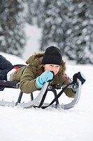Italy, South Tyrol, Seiseralm, Girl 12_13 sledding downhill, portrait