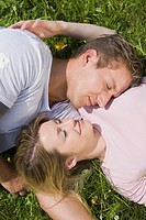 Germany, Bavaria, Munich, Young couple lying in meadow, smiling, elevated view, portrait