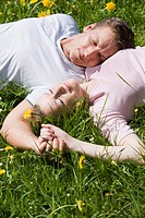 Germany, Bavaria, Munich, Young couple lying in meadow, elevated view