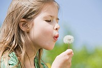 Germany, Bavaria, Munich, Girl 6_7 blowing dandelion seeds, eyes closed, side view, portrait