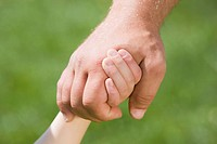 Germany, Bavaria, Munich, Man and child holding hands, close_up