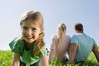 Germany, Bavaria, Munich, Family sitting in meadow, girl 6_7 in foreground, smiling, portrait