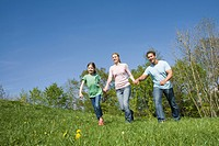 Germany, Bavaria, Munich, Family walking in meadow