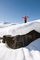 Italy, South Tyrol, Seiseralm, Boy 4_5 standing on snow_covered roof of log cabin