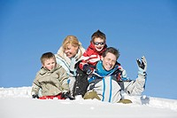 Italy, South Tyrol, Seiseralm, Family sitting in snow, portrait