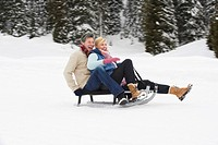 Italy, South Tyrol, Seiseralm, Couple sledding downhill, laughing, portrait
