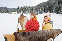Italy, South Tyrol, Seiseralm, Boy 10_11 and girl 12_13 sitting in sleigh, smiling, portrait