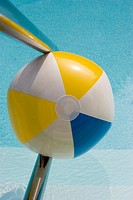 Beach ball stuck in a railing leading down to a swimming pool