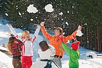Austria, Salzburger Land, Altenmarkt, Family standing by snowman, throwing snow in the air, laughing, portrait