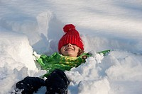 Austria, Salzburger Land, Altenmarkt, Boy 6_7 lying in snow, smiling, portrait