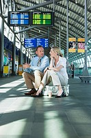 Germany, Leipzig_Halle, Airport Businessman and businesswoman sitting on suitcase