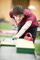 Germany, Bavaria, Young man playing pool outside, portrait