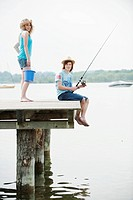 Germany, Bavaria, Ammersee, Young couple on jetty, fishing