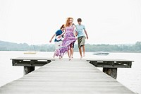 Germany, Bavaria, Ammersee, Four friends jumping on jetty