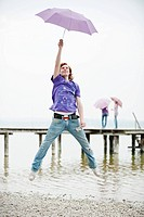 Germany, Bavaria, Ammersee, Young man holding umbrella and jumping