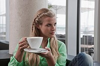 Germany, Cologne, Young woman in cafe holding cup of coffee, portrait