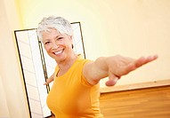 Senior woman with outstretched arms, smiling, portrait (thumbnail)