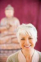 Portrait of a senior woman in background a buddha statue (thumbnail)