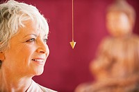 Portrait of a senior woman holding pendulum (thumbnail)