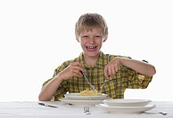 Boy 8_9 eating spaghetti, laughing, portrait