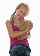 Portrait of girl 10_11 cuddling teddy bear, studio shot