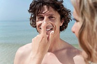 Spain, Mallorca, Woman applying suncream on man´s nose