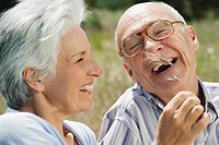 Spain, Mallorca, Senior couple, Woman tickling man with blade of grass, laughing, portrait, close_up