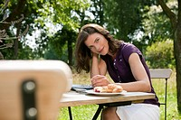 Germany, Hamburg, Woman having breakfast in garden