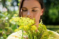 Germany, Hamburg, Woman in garden, smelling flower