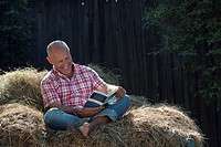 Germany, Bavaria, Senior man sitting on haystack, reading a book