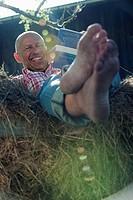 Germany, Bavaria, Senior man sitting on haystack, reading a book