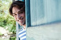 Germany, Bavaria, Man standing next to barn door, smiling, portrait