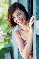 Germany, Bavaria, Woman standing next to barn door, smiling, portrait, close_up