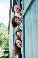 Germany, Bavaria, Four people standing next to barn door, smiling, portrait