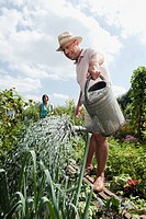 Germany, Bavaria, Senior man watering flowers, woman in background