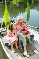 Italy, South Tyrol, Grandmother and grandchildren 6_7 8_9 sitting in rowing boat, elevated view, portrait