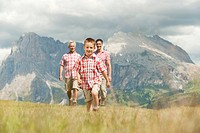 Italy, Seiseralm, Grandfather, Father and son 6-7 walking in meadow, smiling, portrait (thumbnail)
