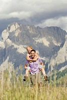 Italy, Seiseralm, Man carrying woman piggyback, laughing, portrait